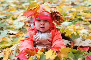 7-months Baby-girl with garland of leafs on head sitting in pile of maple foliages